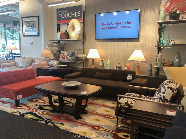 used brown sectional couch, geometric rug, wood coffee table, lamps and wall mounted tv, orange chaise