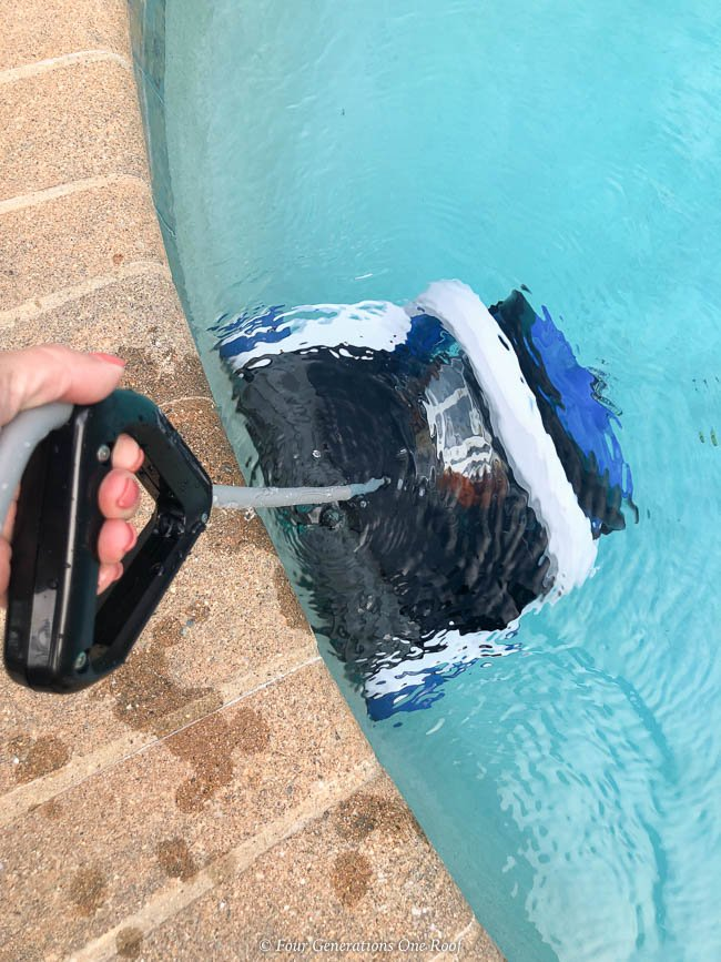 Woman removing the Hayward AquaVac 6 Series robotic pool cleaner from the pool