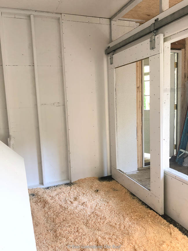 white chicken coop interior and DIY sliding barn door, pine shavings