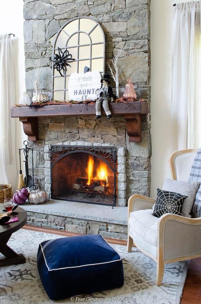 stone fireplace with wood mantel, mirror, spider, blush, purple metallic pumpkins, halloween sign, spider pillow
