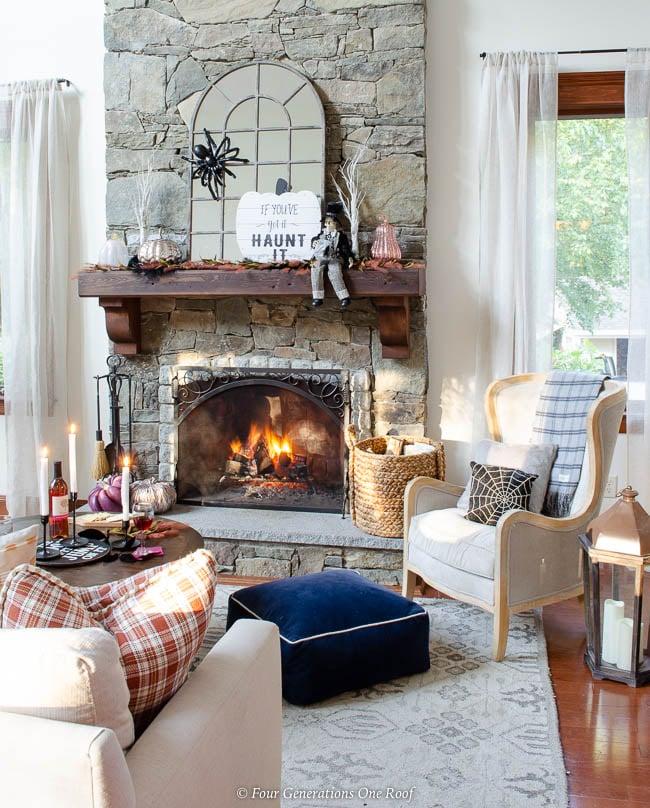 halloween mantel, fall decorations, stone fireplace with wood mantel, burning fire, mirror, spider, blush, purple metallic pumpkins, halloween sign, skeleton