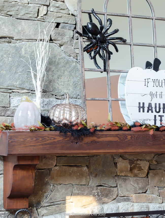 halloween mantel with fall decorations , stone fireplace with wood mantel, burning fire, mirror, spider, blush, purple metallic pumpkins, halloween sign, skeleton