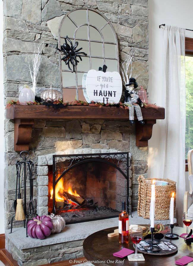 Halloween mantel, stone fireplace with wood mantel, burning fire, mirror, spider, blush, purple metallic pumpkins, halloween sign, skeleton