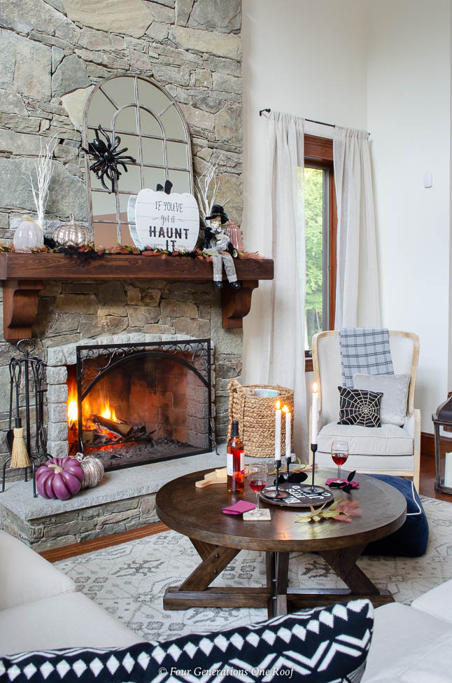 Tips on decorating a Halloween mantel with Fall decorations + stone fireplace with wood mantel, burning fire, mirror, spider, blush, purple metallic pumpkins, halloween sign, skeleton