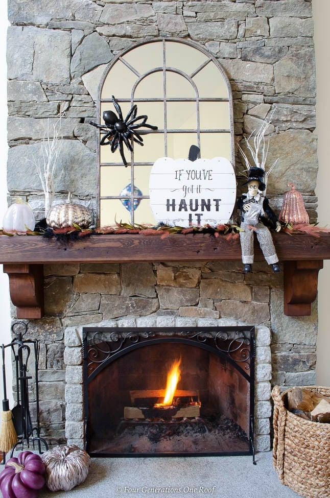 stone fireplace with wood mantel, burning fire, mirror, spider, blush, purple metallic pumpkins, halloween sign, skeleton