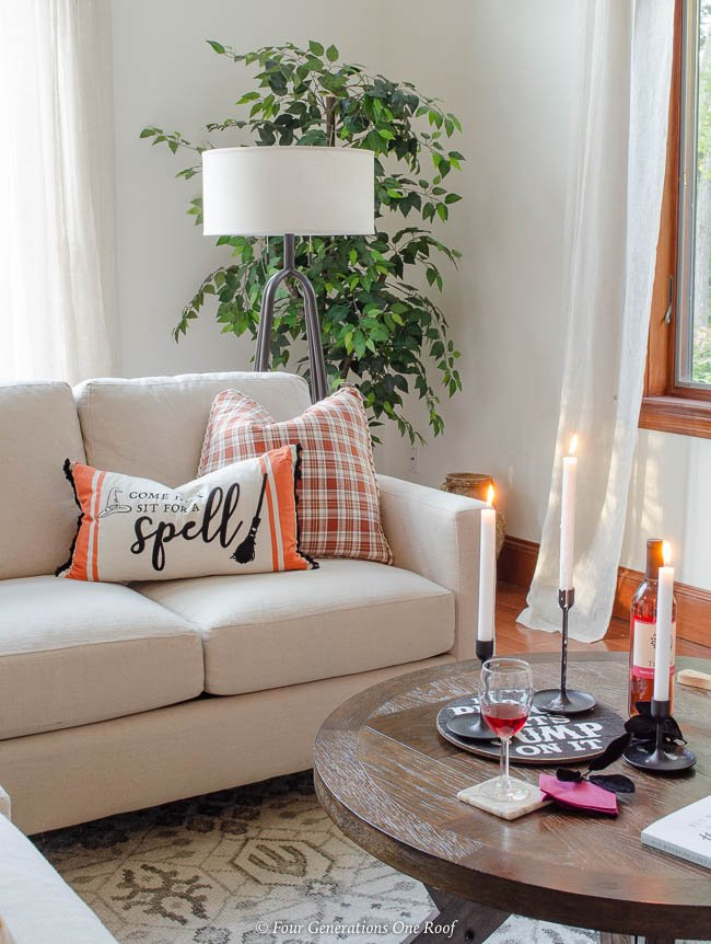 Halloween living room orange plaid pillow, orange halloween pillow, black candles sticks with candles, white sectional couch
