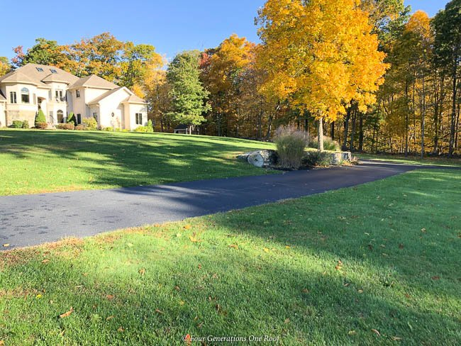 long driveway, stone retaining wall, mediterranean house, fall colorful leaves