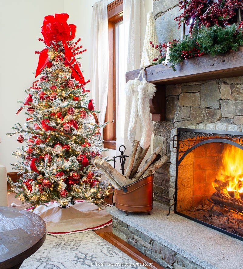flocked christmas tree decorated 5 ways , white black rug, red plaid ornaments, red cardinals, red vintage truck ornaments, red bow, pine wood logs, metal wood bucket, stone fireplace with fire