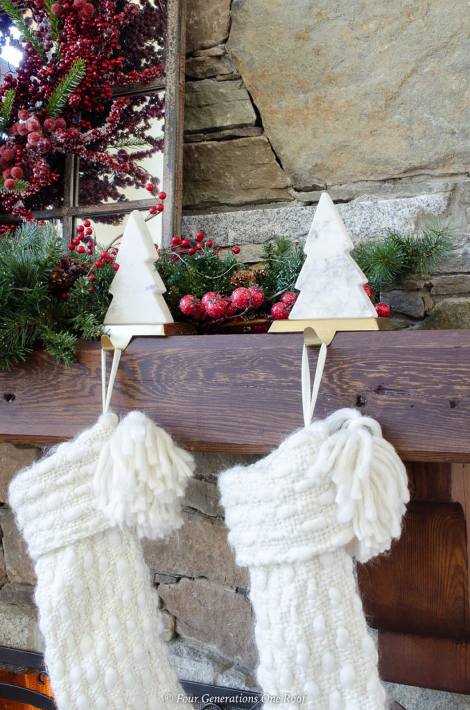 holiday brown wood mantel, white cable knit christmas stockings, white marble tree stocking hangers, garland