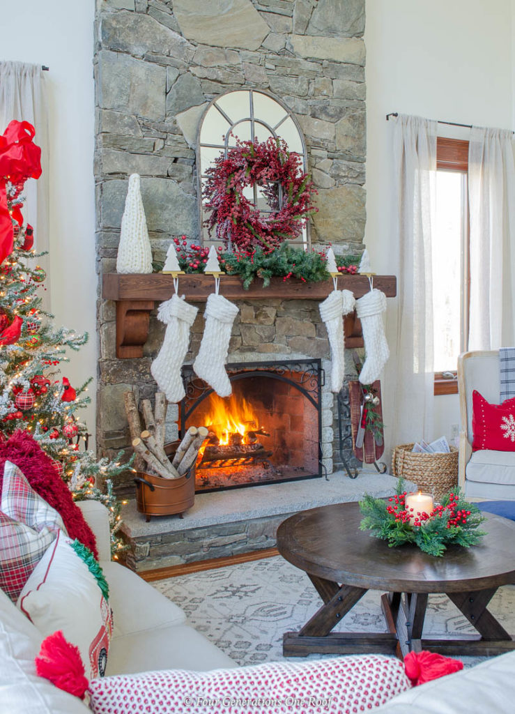 holiday brown wood mantel, white Christmas stockings, cranberry wreath, coffee table with candle ring, red christmas tree with red bow, fire in stone fireplace