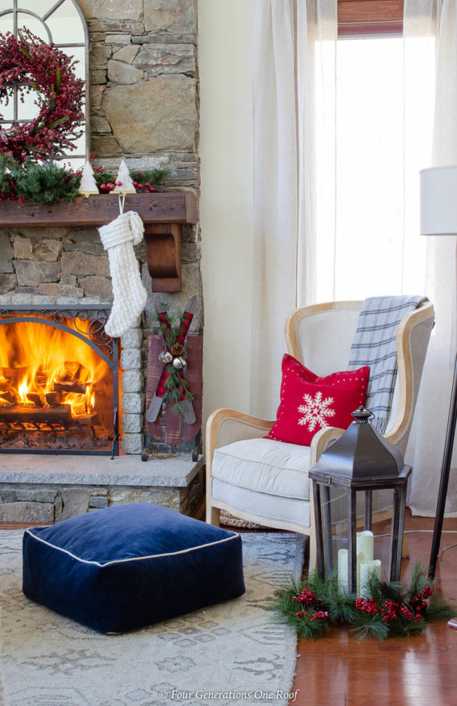 white wood accent chair, red snowflake pillow, blue floor pouf, stone fireplace with fire, holiday brown wood mantel, white knit stocking