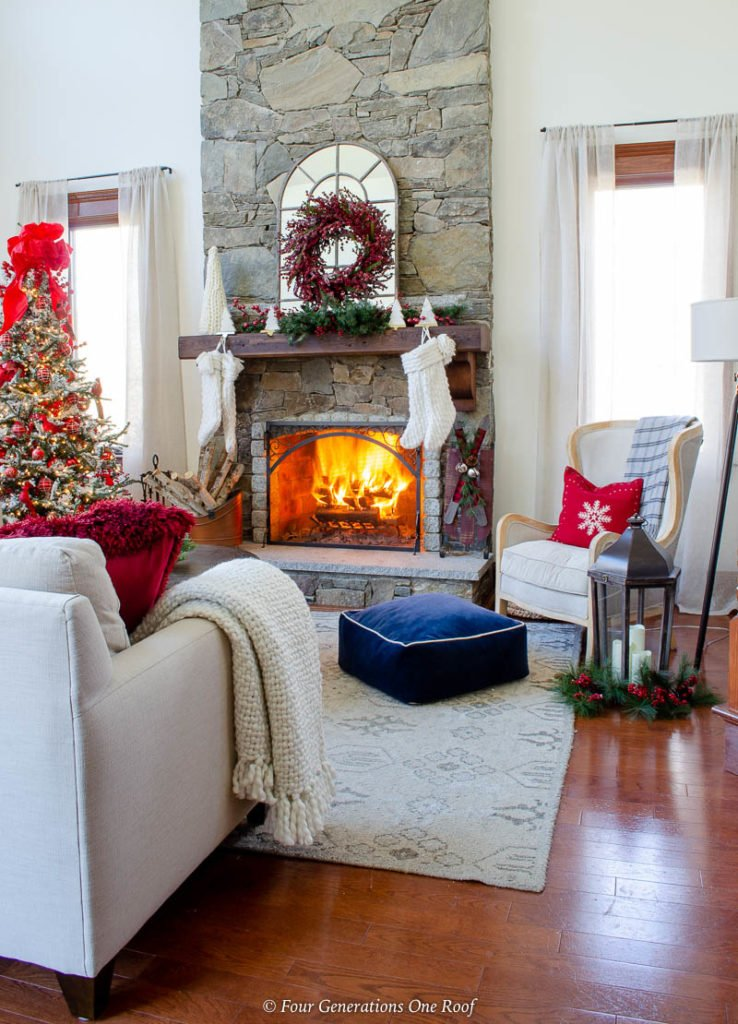 holiday brown wood mantel, white Christmas stockings, cranberry wreath, fire in stone fireplace