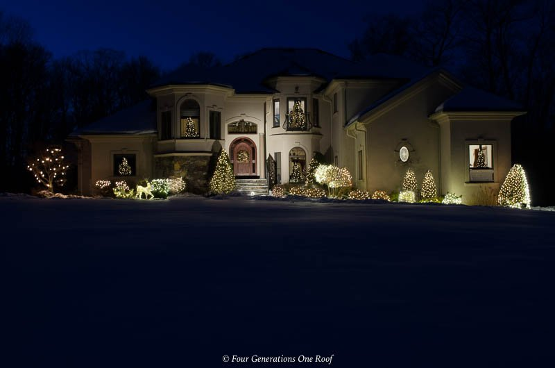 large stucco home with bright outdoor christmas lights, front door spot light and Christmas sleigh and reindeer