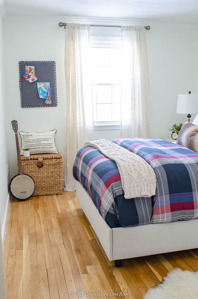 small white bedroom, one window, sheer drapes, plaid bedding, seagrass basket, bango, velour bedrails