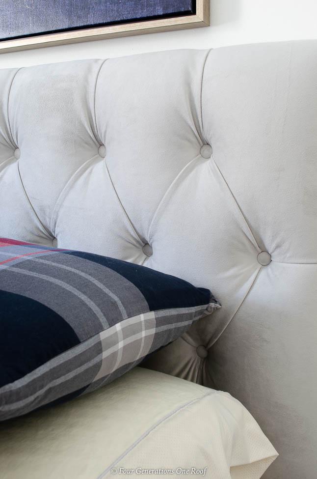 Gray tufted headboard, plaid pillow case