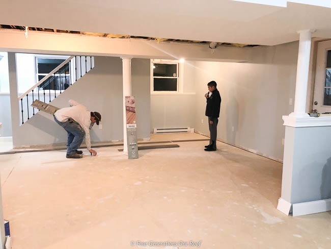 Basement remodel renovation with cement floor, white beams and white lally columns