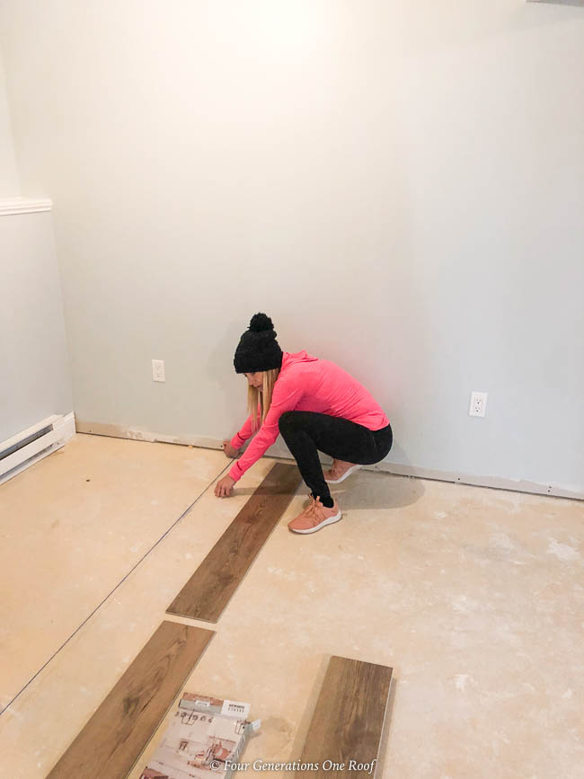 Snapping a chalk line to start the diy vinyl flooring over cement project in the basement