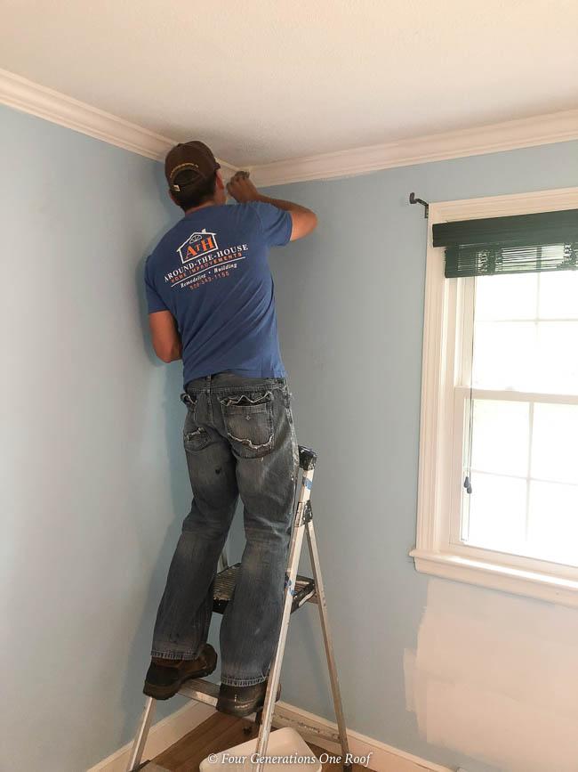 man applying white primer over blue walls in a bedroom