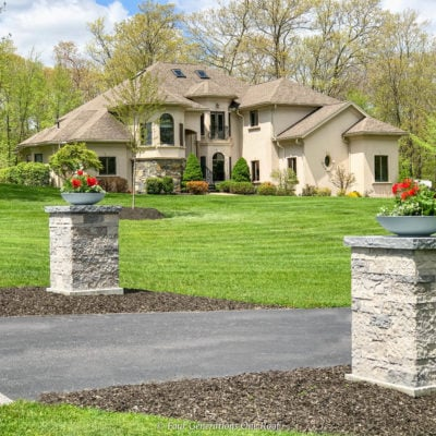 stone driveway entrance columns with grey bowl planters filled with geraniums + stucco house
