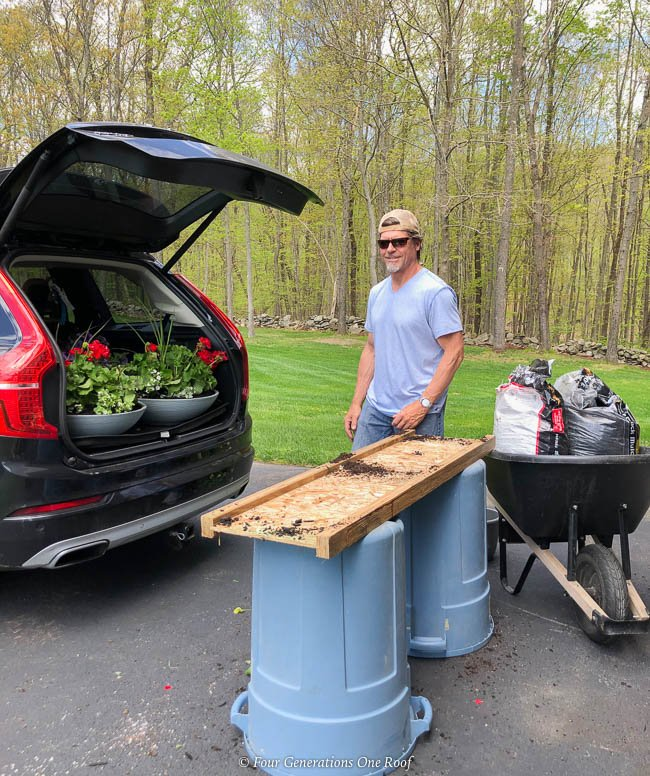 outdoor gardening table with 2 garbage barrels and a piece of plywood