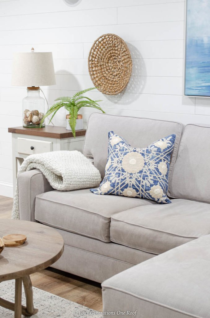 basement makeover with white ceiling and vinyl floor planks- white plank wall, grey couch, blue medallion pillow, seagrass wall accent, coastal wall art