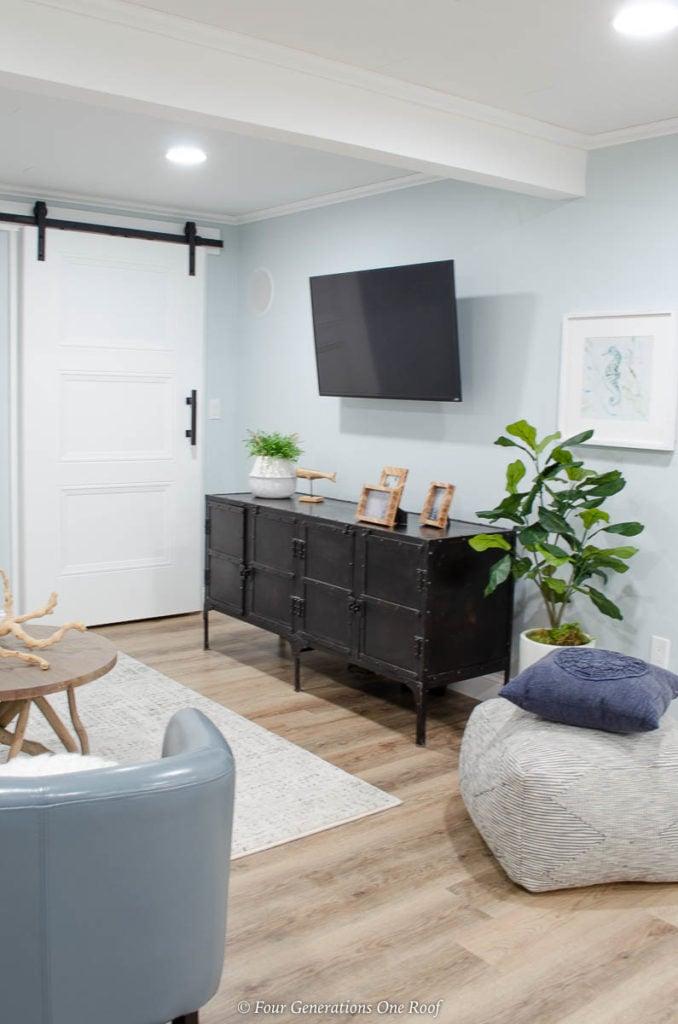 driftwood vinyl plank floor,black restoration hardware console, barn sliding door, lullabye blue walls