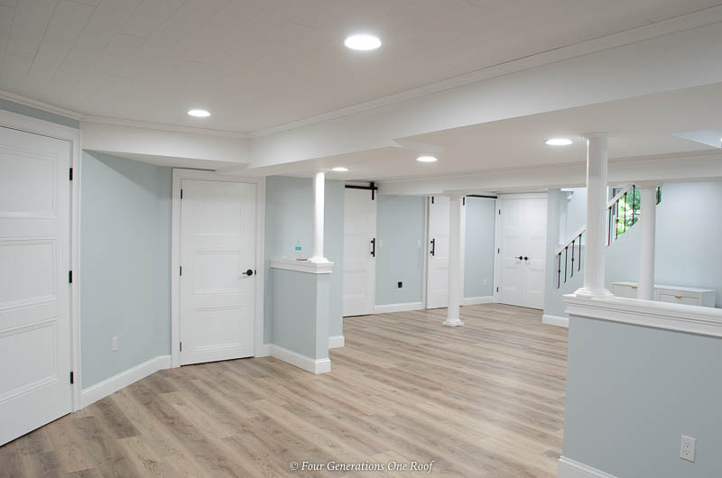 basement makeover with white ceiling and vinyl floor planks-harvest oak color Select Flooring vinyl plank flooring, masonite livingston white interior doors, basement columns, Armstrong ceiling planks