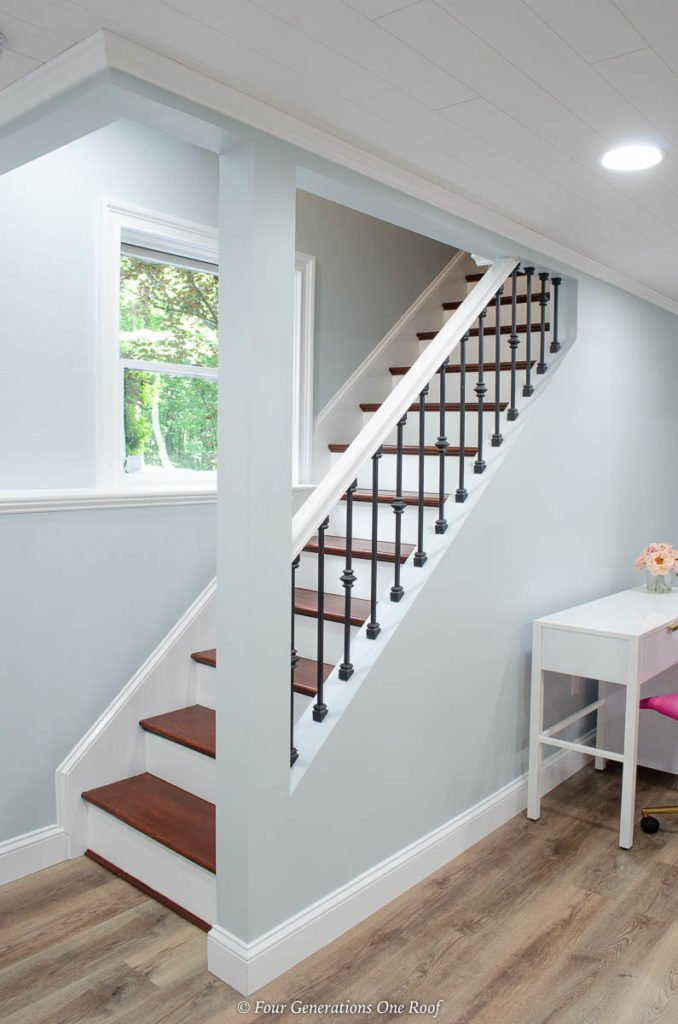 basement stairs with iron balusters, harvest oak vinyl plank flooring, blue walls