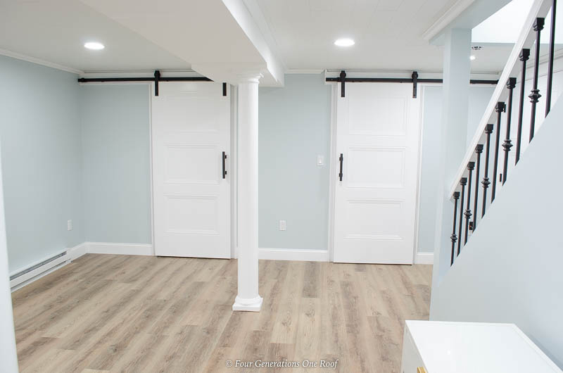 Masonite Livingston Interior Doors on black barn sliding hardware, harvest oak driftwood style flooring, blue walls