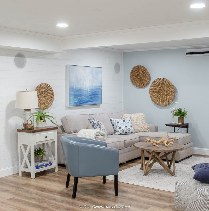 basement makeover with white ceiling and vinyl floor planks-driftwood planks, white plank wall, modern coastal basement family room, blue walls, seagrass baskets on walls