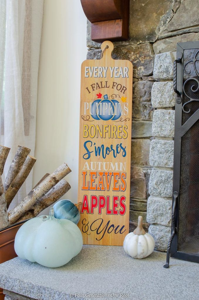 Blue pumpkin, Fall wooden sign on stone fireplace hearth with logs