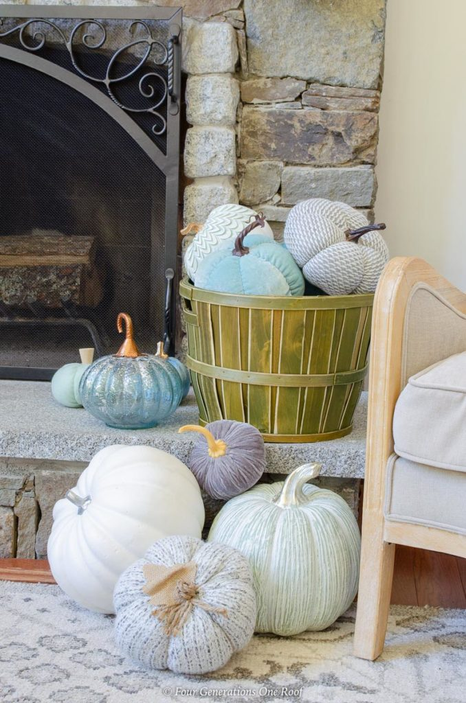 Green apple basket filled with blue Fall velvet and wood pumpkins fireplace hearth