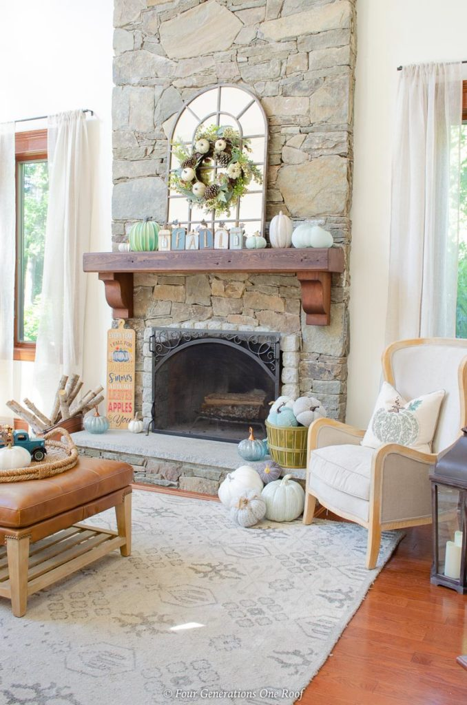 fireplace with blue and white pumpkins in basket with accent chair