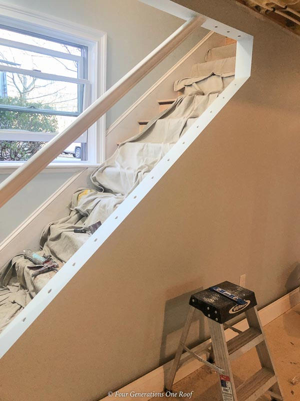 basement stairs with cutout for handrail and drilled baluster holes and sheetrock wall