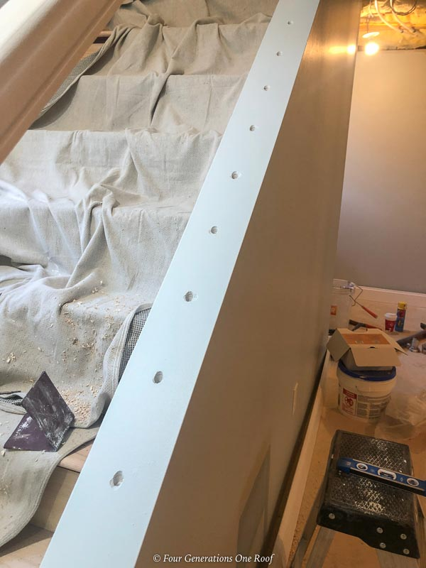 Open basement staircase with drilled holes for installing balusters