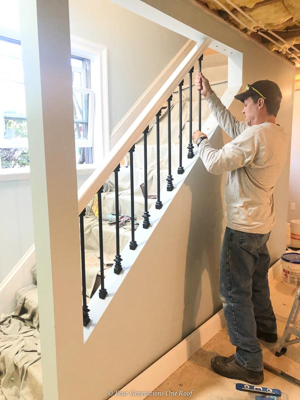 Open basement stairs with black iron balusters Installation