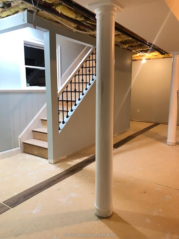 open basement staircase with black iron balusters and custom lally column