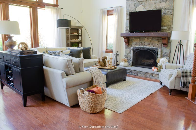 Neutral living room, tv on mantel, cathedral ceiling, white sectional, black sofa wine table, stained trim