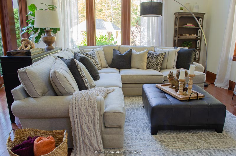 Large White Sectional Living Room, cream rug, black leather ottoman, cathedral ceilings