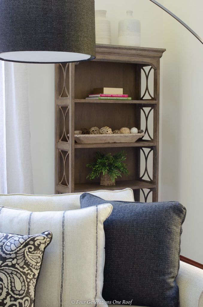 """74"""" light brown bookcase, arched floor lamp, white sectional"""