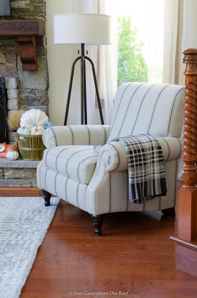 white and navy pin striped accent chair, black iron floor lamp