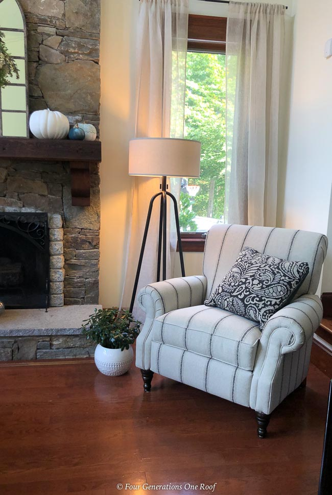 white and navy striped push back recliner, black iron floor lamp, pumpkins on wood mantel
