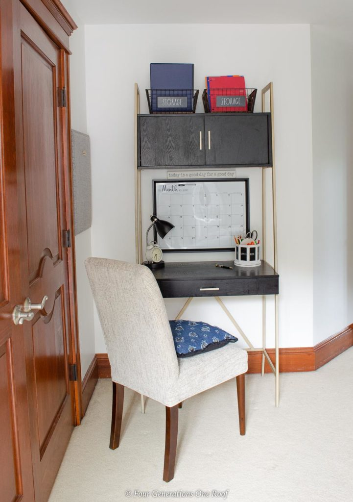 teen bedroom workspace, black and gold tall desk, built in cabinets, chair, wall calendar