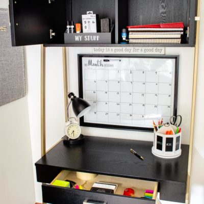 black and gold tall desk, cabinet doors, pull out drawer, wall calendar, storage baskets, pencil holder from Homegoods
