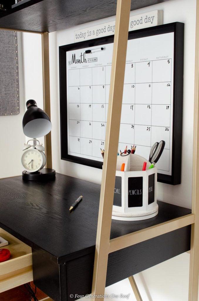 black and gold tall desk, white pencil holder, black desk lamp, wall calendar dry erase