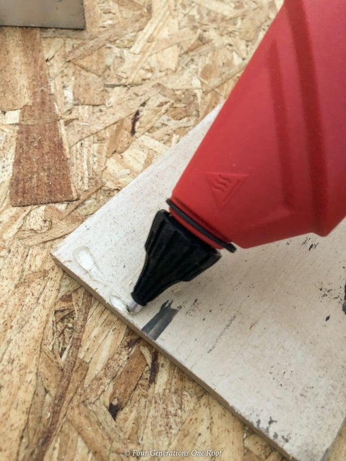 Arrow glue gun glueing wood floor planks together