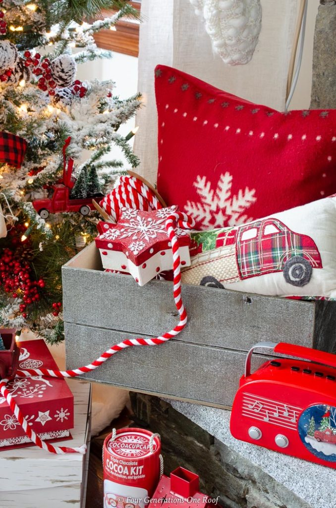 DIY gray wooden Christmas crate filled with red snowflake pillow, presents, red striped ribbon, red vintage boom box