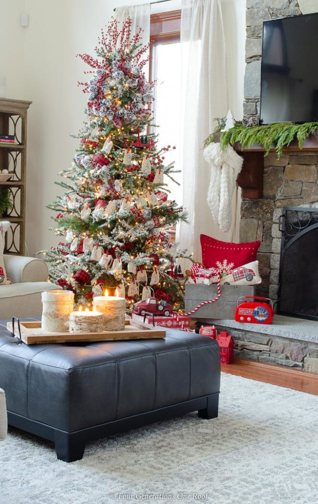 red and white flocked christmas tree, black leather ottoman, gray Christmas crate with gifts
