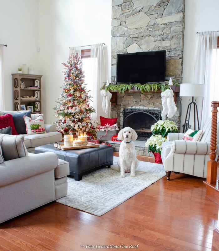 flocked christmas tree, goldendoodles, red christmas ornaments, red pillows, black ottoman coffee table, stone fireplace, wood mantel, tv over mantel, white sectional