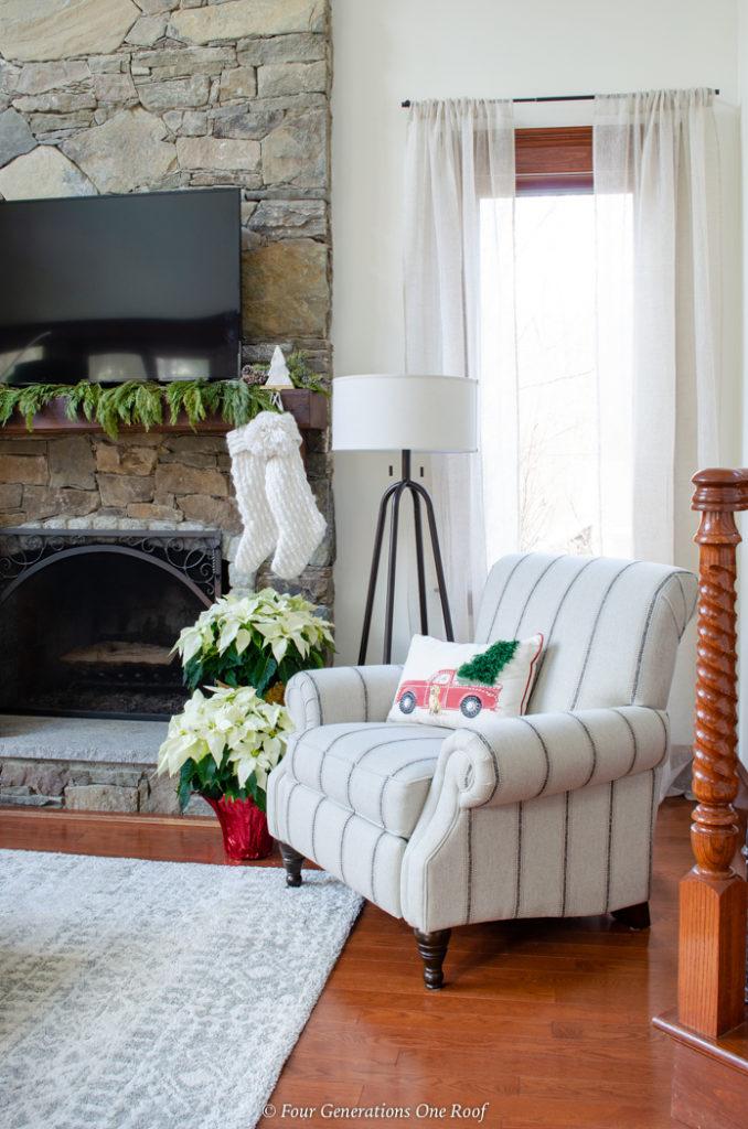 stone fireplace, wood mantel white stocking, white striped recliner chair, white poinsettias